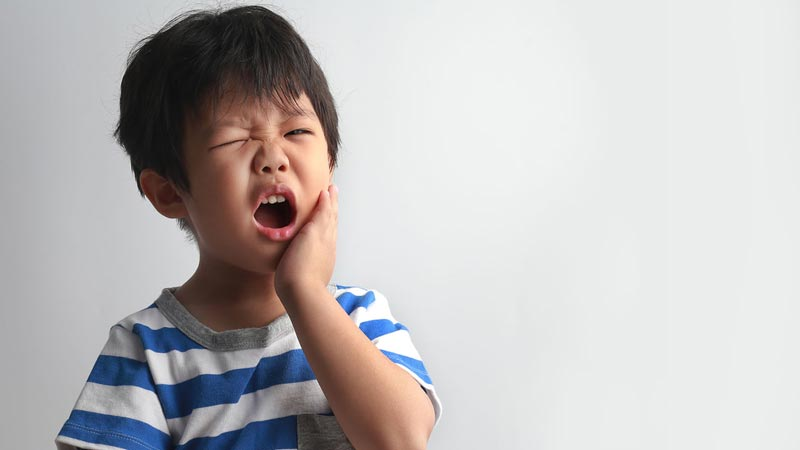 Child holding mouth in pain